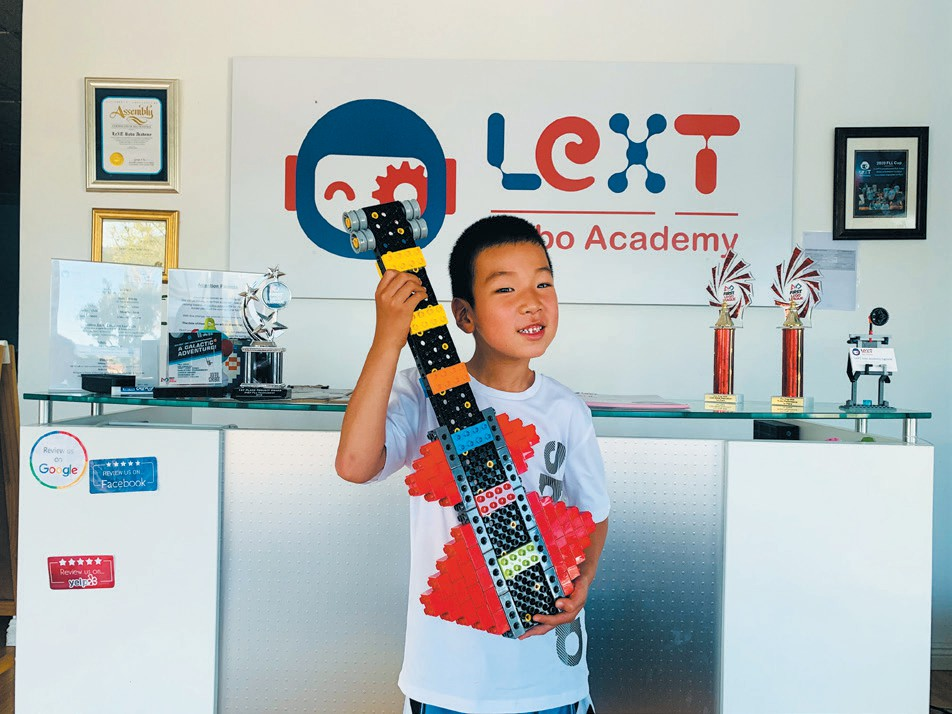 HAPPY PLACE—Building Legos makes this guy really happy. Ryan's guitar was built with the Tech Machines set using a Lego screwdriver to afix the building blocks and interlocking structures. Created by Ryan Chen, age 6