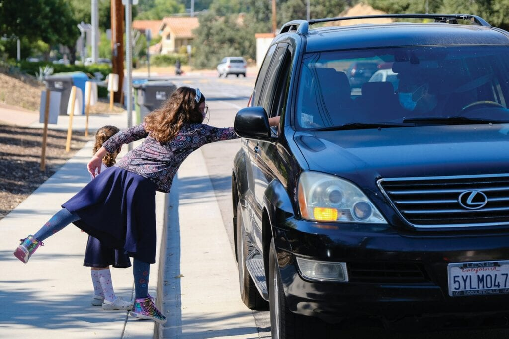 """HEALTH AND SAFETY—Above, Malka Friedman, 10, hands a pack of face masks to a motorist July 21 at the Chabad of Calabasas on Old Topanga Canyon Road. Each pack contained five masks. Chabad's goal was the delivery of 2,000 masks at no cost to the public. At right, Rabbi Eli Friedman alerts motorists of the offer while his 5-year-old daughter Liva assists. """"We are hear to uplift others, while providing for basic needs, and right now people need masks and a message of hope,"""" Friedman said."""