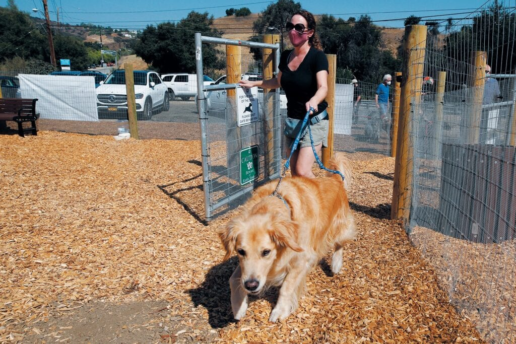 HAPPY PEOPLE, HAPPY PUPPIES—At left, Calabasas Mayor Alicia Weintraub and her dog, Duke, are the first ones to enter the temporary dog park at Wild Walnut Park during the Sept. 4 opening. Above, the dog park's sign. Top right, Calabasas resident Roza Besser has her Labradoddle, Reggie, 4, do a trick inside the park.