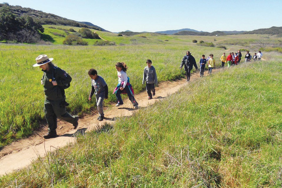 ON THE SCENE—At top, a park ranger leads children on an education hike in the mountains. Above, a hawk with prey and, at left, a climber ascends Ladyface Mountain in Agoura Hills.